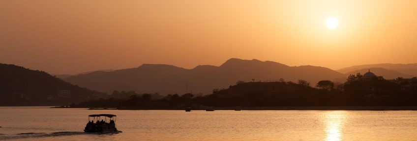 A golden-brown sunset over Lake Pichola