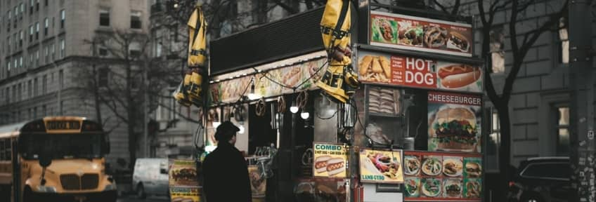 A man standing in front of a hot-dog cart
